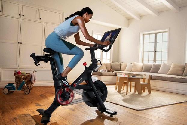 woman using peloton bike at home