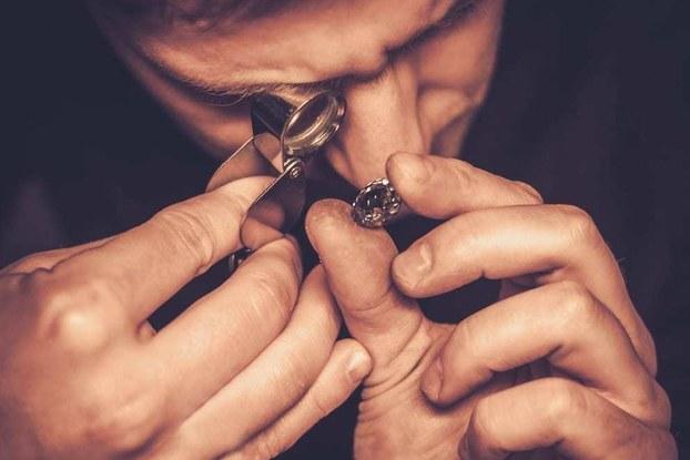 Man looking at diamond through loop