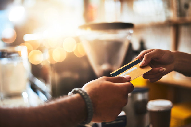 Women handing credit card to barista