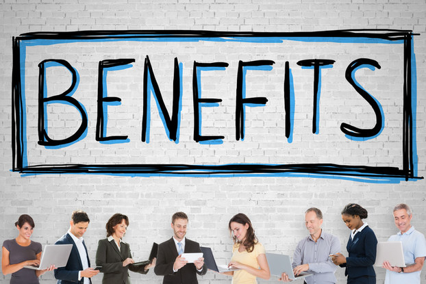 Employees standing under benefits sign