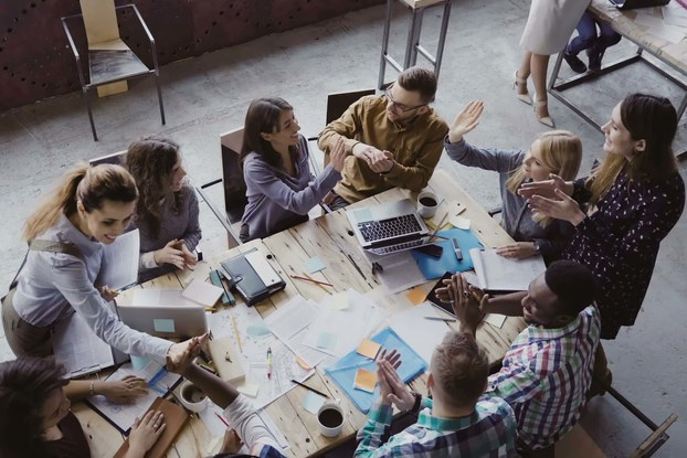 Overhead photo of employees high fiving at work table