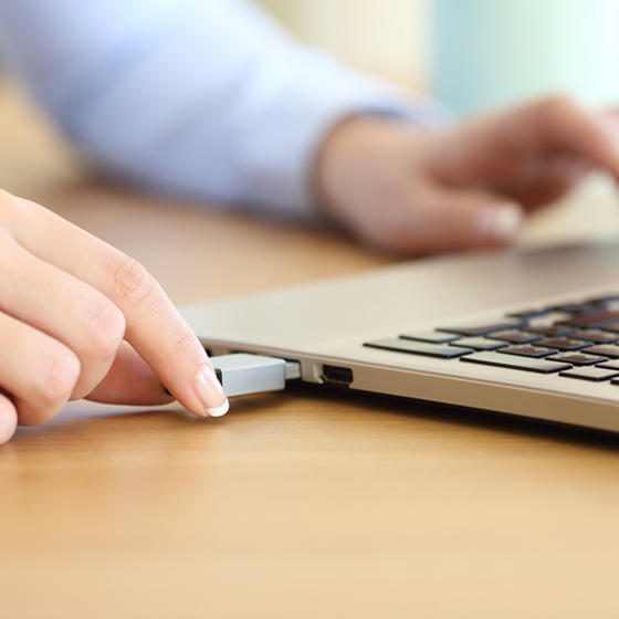Workers plugging thumb drive into laptop