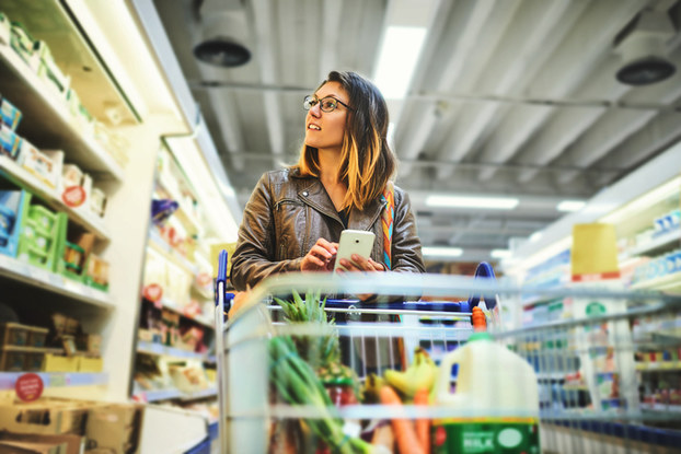 Woman using smartphone in grocery store