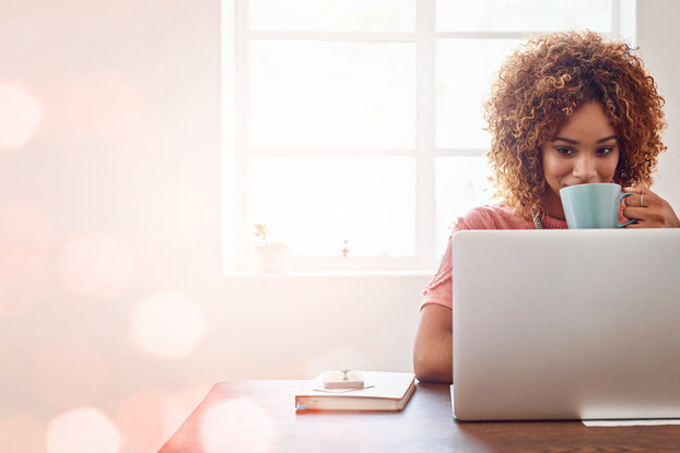 Woman with coffee using laptop