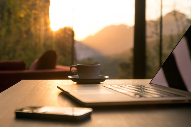 Coffee next to laptop by window