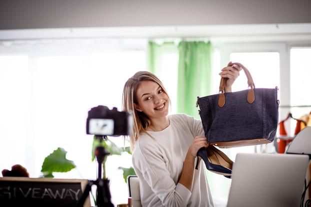 female influencer holding pocketbook in front of camera