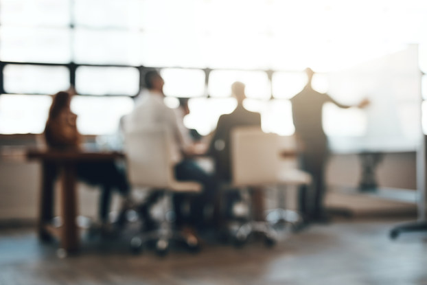 blurred image of a group of employees in a meeting