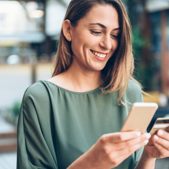 woman shopping on phone with credit card