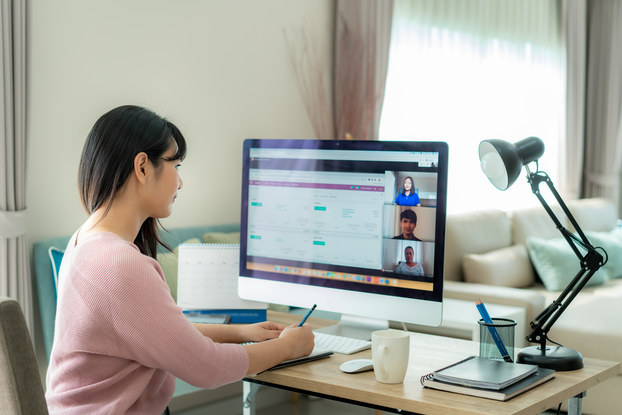 Woman video chats at desk.