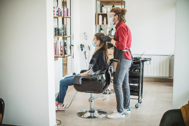 woman getting hair done in salon with masks on