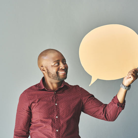 man holding speech bubble cutout