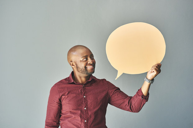 man holding speech bubble cutout