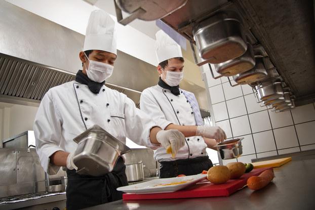 employees working in kitchen wearing masks