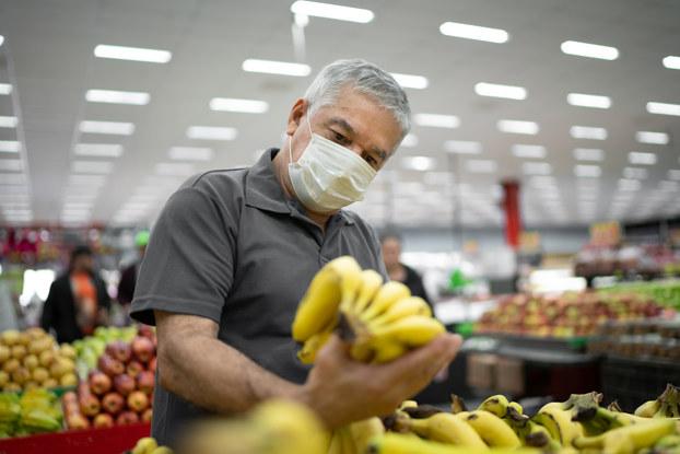 man in supermarket looking at bananas