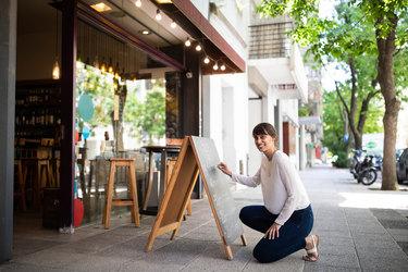 woman outside shop writing on chalkboard
