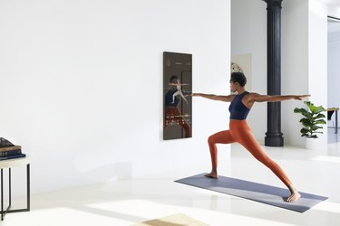 woman using mirror for home exercise