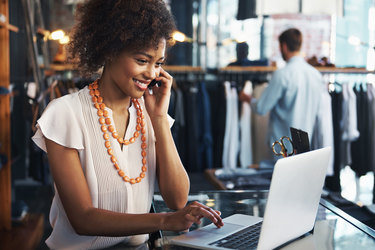 woman working in store on laptop