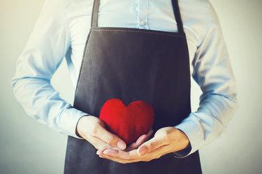 employee wearing apron holding heart
