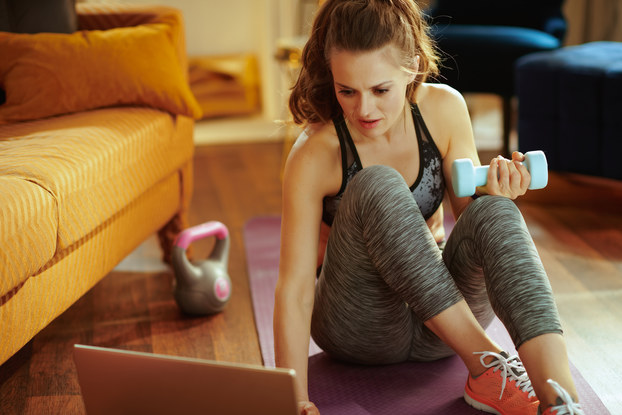 woman exercising at home watching laptop