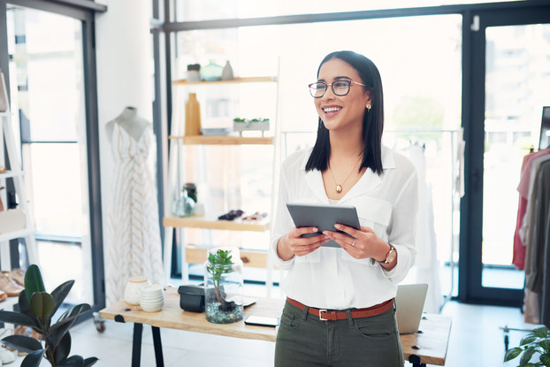 woman small business owner in shop on tablet