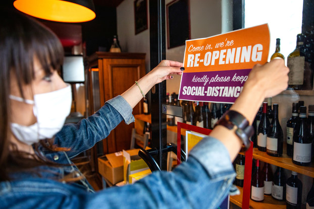 woman putting up reopening business sign