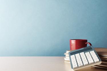 calculator and coffee mug on a tabletop