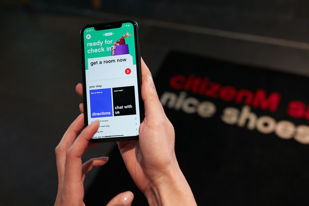 person holding phone with citizenM app open