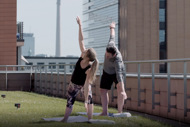 two people doing rooftop yoga at hyatt hotel