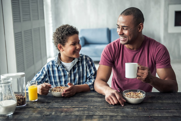 father and son at breakfast table eating cereal