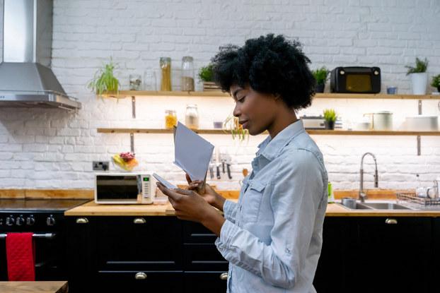 woman in kitchen going through her mail