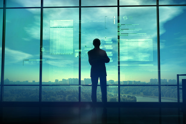man looking out window with coding text in background