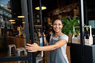 hispanic business owner opening door