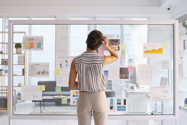 woman writing on clear board in office