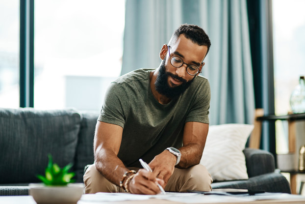 man writing on pad in living room