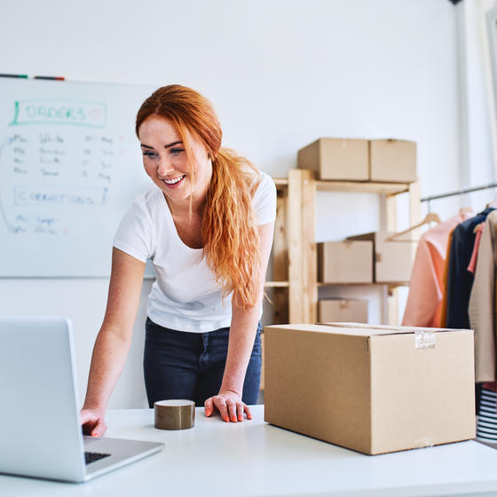 woman on laptop boxing up products