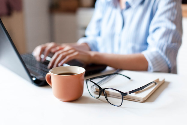 person working remotely at desk with coffee
