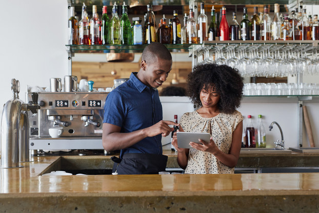 two businesspeople behind bar looking at tablet