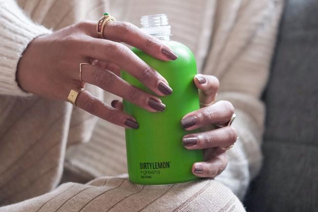 woman holding dirty lemon beverage