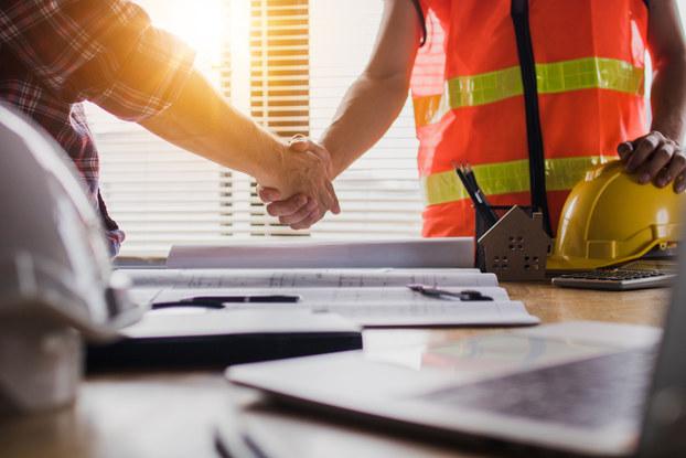 Construction worker shaking hands at desk