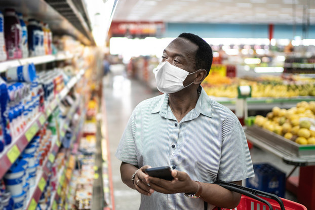 man shopping in supermarket with mask on