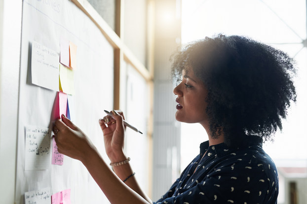 woman working and writing notes on whiteboard
