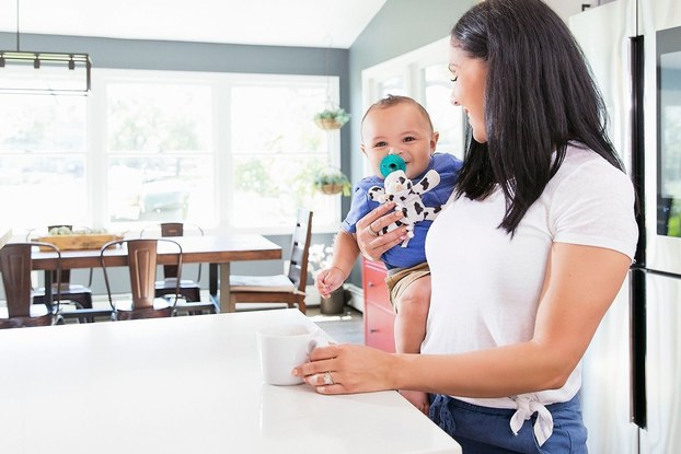 mom holding baby in kitchen with wubbanub pacifier