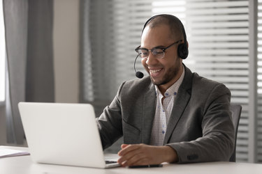 A man wearing a headset sits in front of a laptop.