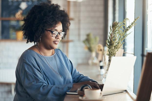 A woman works on her laptop near a window.