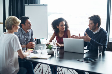 A team of four works around a conference table.