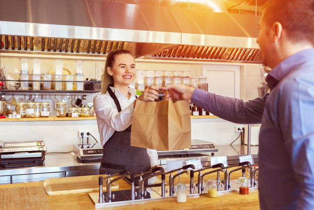 A woman in an apron stands behind a wooden counter and hands two paper bags to a customer.