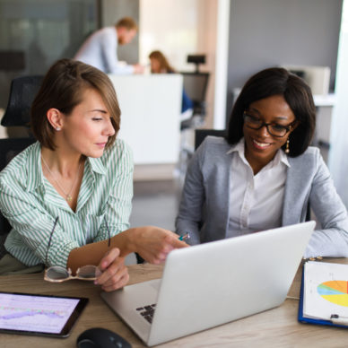 two women looking at laptop screen with charts