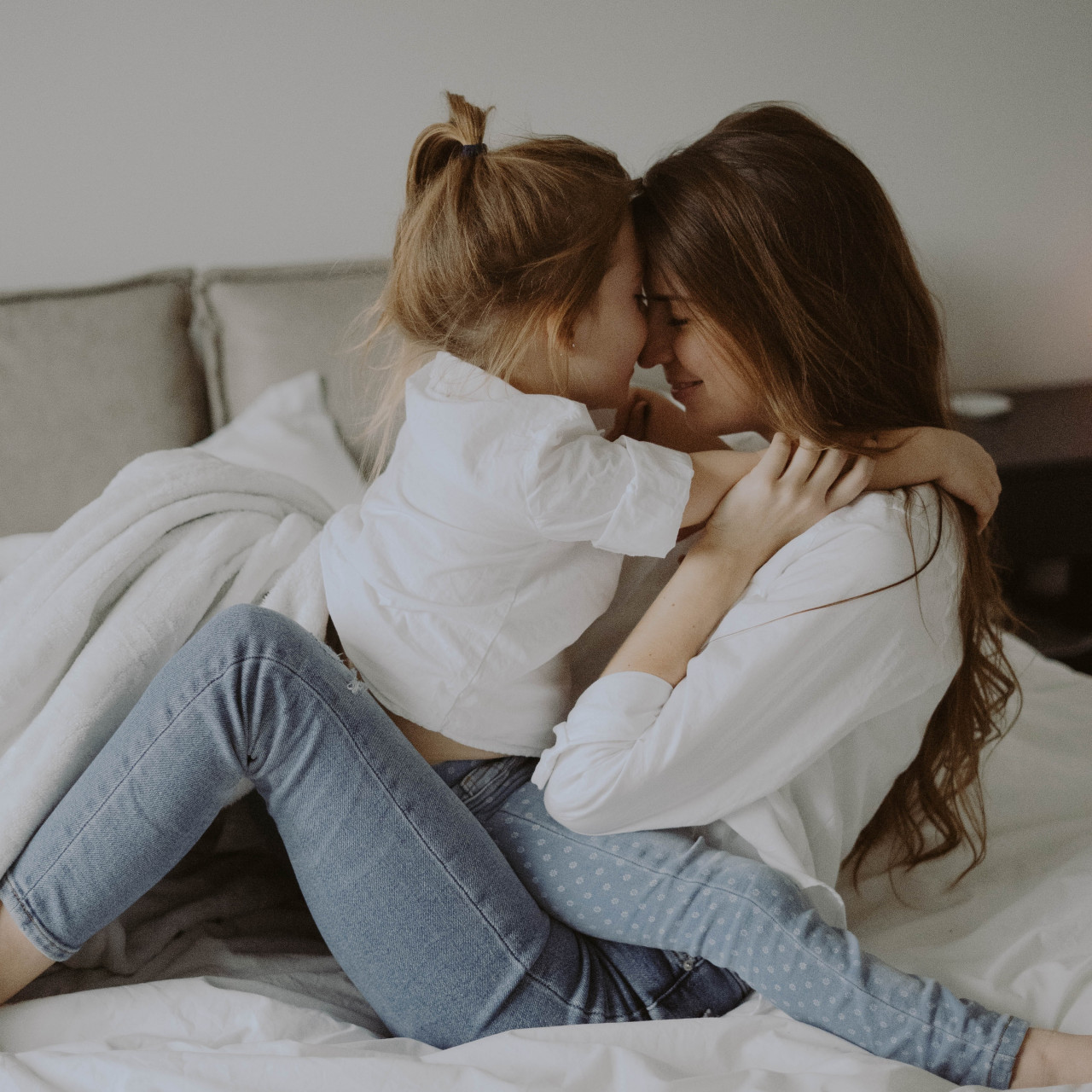 mother and child embracing in bed