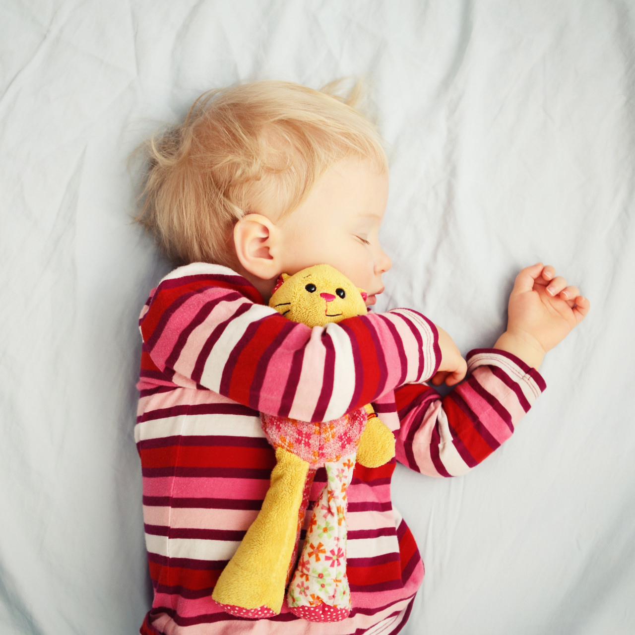 child asleep in bed cuddling a soft toy