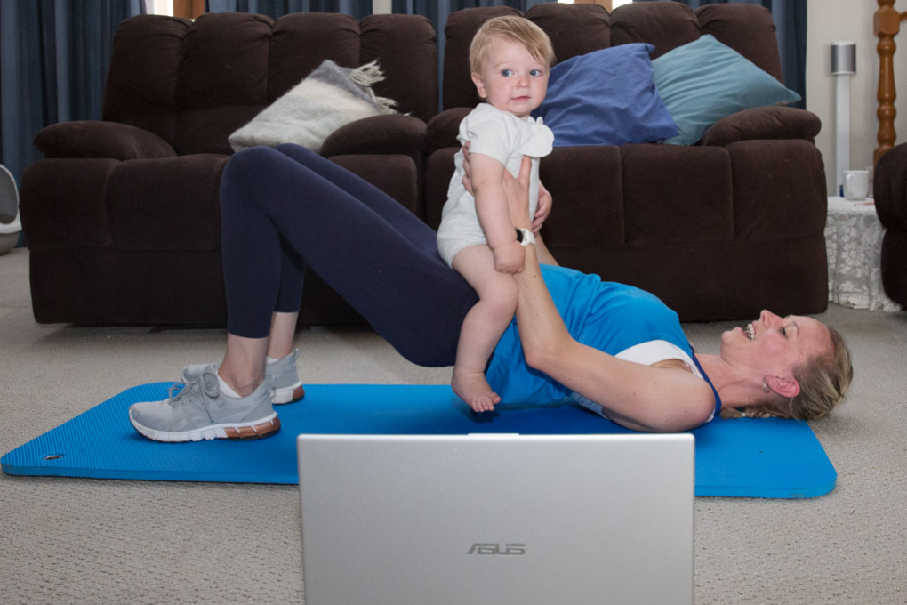Mum and bub exercising online with laptop open